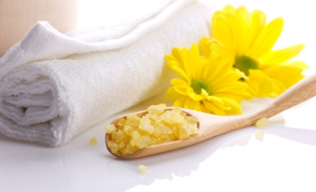 sea flowers: spa still, white towel, salts in wooden spoon and yellow flowers on white
