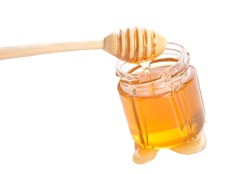 cold remedy: honey in jar with drizzler izolated on white