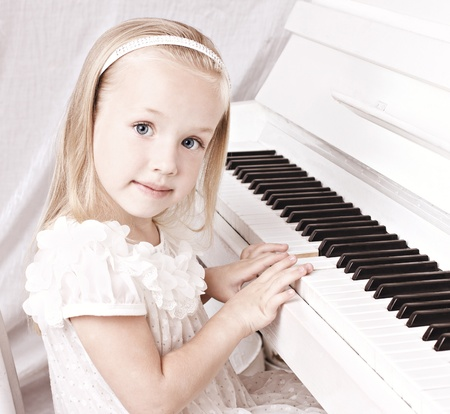 teaching music: little beauy blond girl in white beautiful dress  sitting at white piano, looking at camera  Stock Photo
