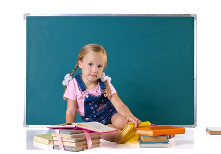 schoolgirl uniform:  little sitting girl with blond pigtails, near learning many multicolored  books, back from blackboard, isolated on white