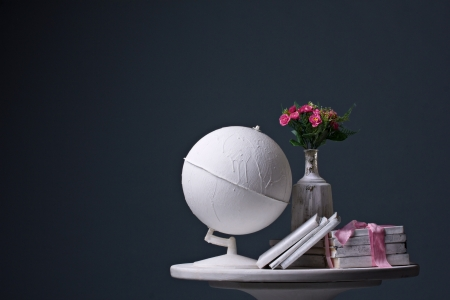 old  white globe, old white  books and branch of pink flower in white carafe standing on white round table on dark background photo