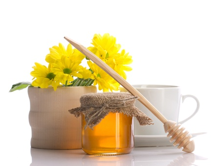 herbal remedy: still of honey, drizzler, flowers and teacup isolated on white Stock Photo