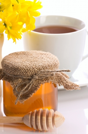 remedy:  closeup of honey,  tea in teacup and yellow flowers  on white background