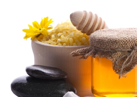 closeup of spa accessories, stones, bath salt and honey on white background photo