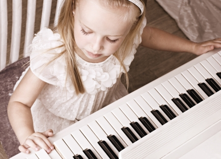 teaching music: little beauty well-dressed girl  playing on white piano, top view