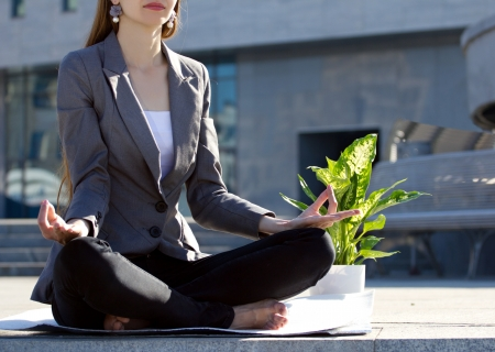 businesswoman sitting in yoga pose, near - flower in pot, on blurred building  background photo