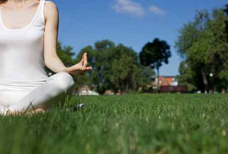 siting: girl in white clothes siting in yoga pose on green grass in park, closeup