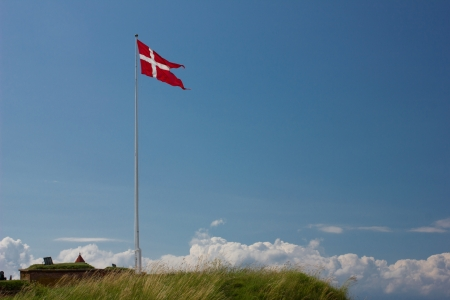 Danish flag on flagstaff, on green grass, on short  building and  blue sky with clouds background photo