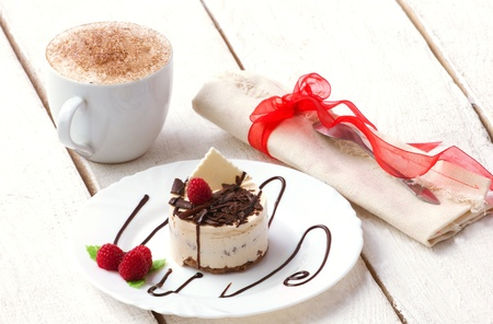 coffee with cream and delicious dessert with chocolate and raspberry on white plate on wooden plank white table photo