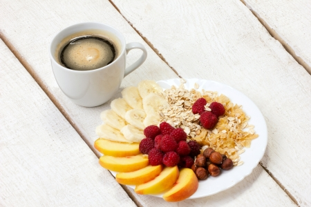 light breakfast: light healthy breakfast - coffee with fruits, nuts and flakes on white wooden plank table
