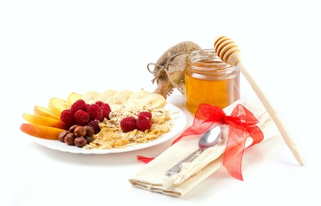 appetize: fresh fruits and berry, nuts and flakes in  with honey isolated on white