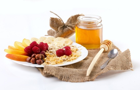 beautiful still - nuts, flakes, peach and raspberry on a plate,  honey, drizzler and spoon on sacking ,  isolated on white Stock Photo - 21816478