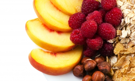 beautiful colorful  dessert with peach, berry, nuts and flacks on white background, closeup, top view photo