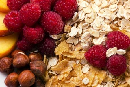Mixed of beautiful colorful fresh fruits, raspberry, nats, and flakes, macro photo