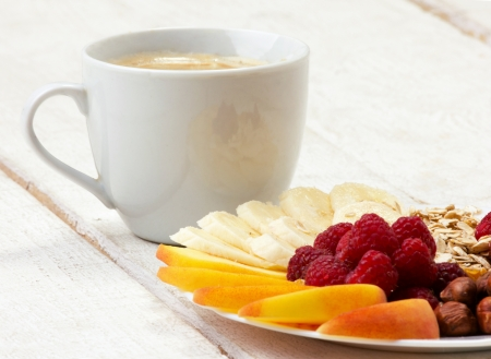 appetize: coffee and vitamins dessert with fruits, berry, nuts and flakes on white wooden table Stock Photo