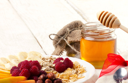 light breakfast: wholesome breakfast - muesli with nuts, fruits, berry and honey on white wooden table Stock Photo