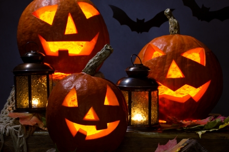 laterns: halloween pumhkins and bat with laterns and maple leafs on dark background Stock Photo