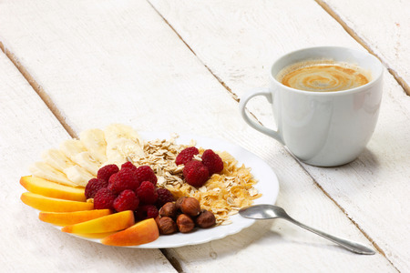 appetize: vitamins breakfast - muesli with berry, fruits, nuts and coffee on white plank table