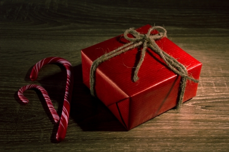 gift red box and candy cane on wooden background photo