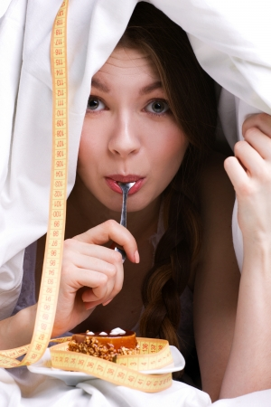 furtively: young beautiful woman under white cover eating cake, near - measure