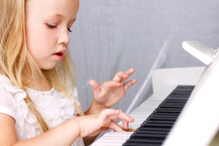 light play: little blond girl in beautiful white dress plaing on white piano, closeup  Stock Photo