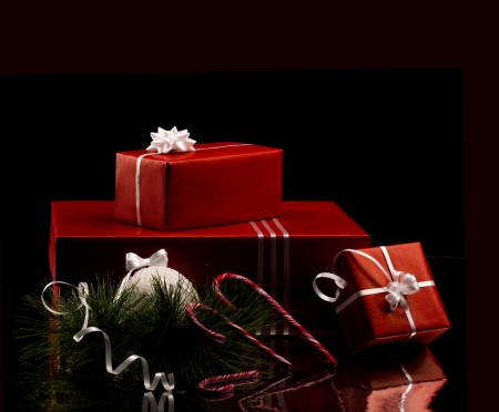 christmas still - several red boxes with white bow, candycane and branch of firtree on black dark background Stock Photo