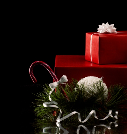 christmas card with red gift boxes, white ball, branch of fir tree and candy cane on black background Stok Fotoğraf