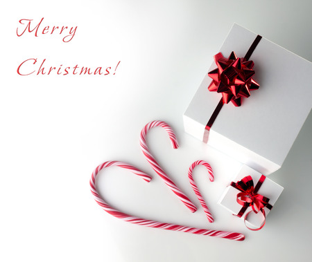 christmas postcard - gift white boxes with red bow and sticks of candycane on white-grey background photo