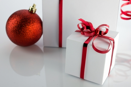 christmas presents white boxes with red bright bow and ball, closeup photo
