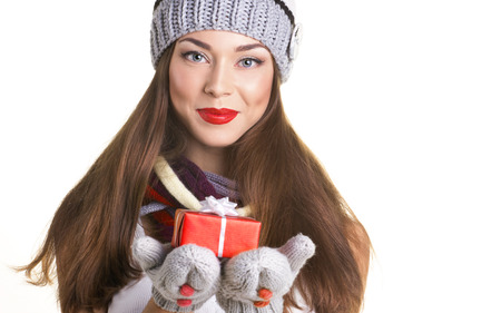 portrait of a beautiful young woman in winter clothing with gift box on white background photo
