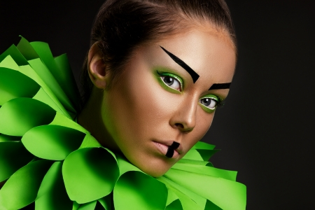 eccentric: closeup portrait of a fashion young woman with eccentric green make-up on black background