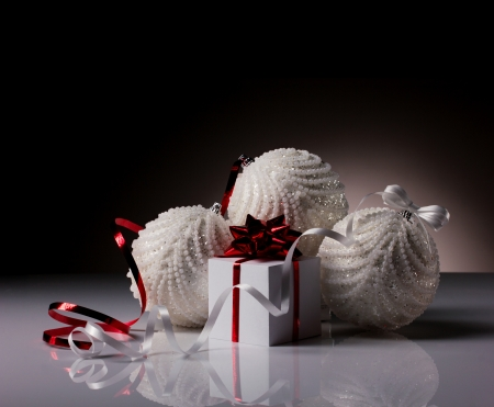 white gift box and three christmas white balls with bright bow on dark grey background photo