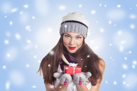 young woman in hat and gloves with  gift red box on blue and snow background photo