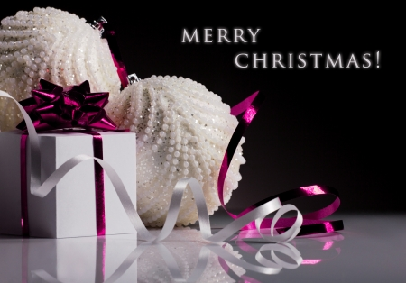 christmas white  ball and gift box with pink bow on black background photo