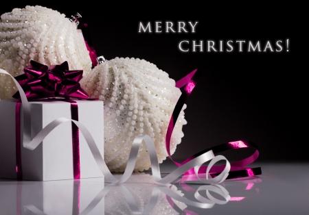 weihnachtsschleife: Weihnachten wei�e Kugel und Geschenk-Box mit rosa Schleife auf schwarzem Hintergrund