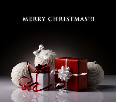 present red and white boxes and christmas balls on grey-dark and black background photo