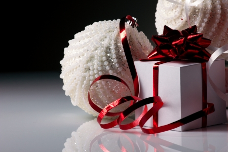 christmas white balls and gifts white box with bright bow on grey light and dark background photo