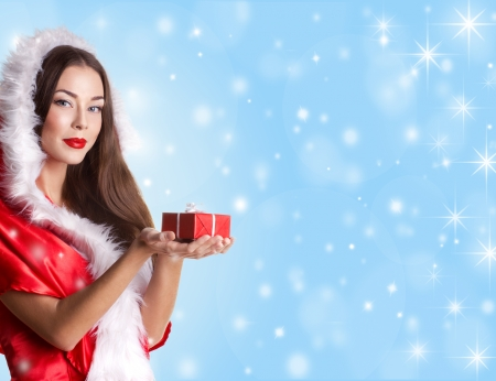 costum: beautiful adult girl in red christmas costum with present red box on blue sky, snow and star background