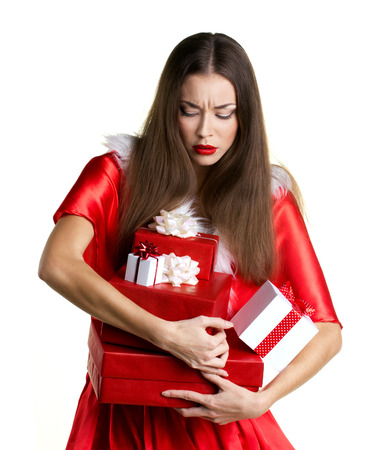 costum: beautiful adult girl in red christmas costum with effort holding pile presents  boxes on white background