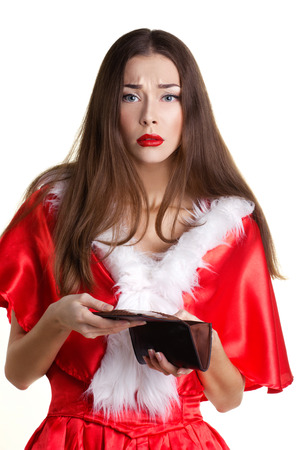 young beautiful  sad woman in red christmas dress with empty purse on white background photo