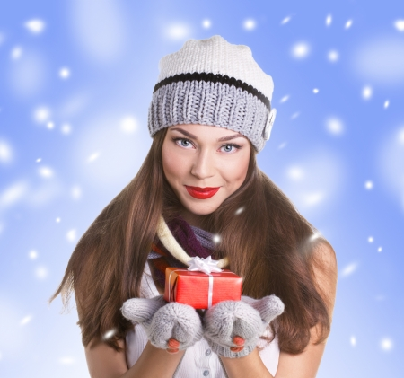 young woman in hat and gloves with  gift red box on snow and blue sky  photo