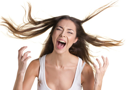portrait of a screaming young woman in white tank top with long flying hear on white background
