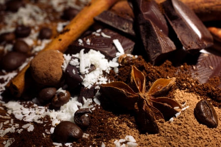 close-up of chocolate mix, coffee beans and coconut flakes with cinnamon stick and anise  photo