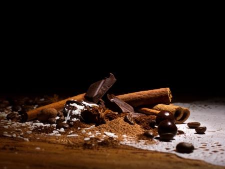 cafe bombon: mezcla de chocolate - bombones, chocolate roto y granos de café con canela y anís sobre fondo negro oscuro Foto de archivo