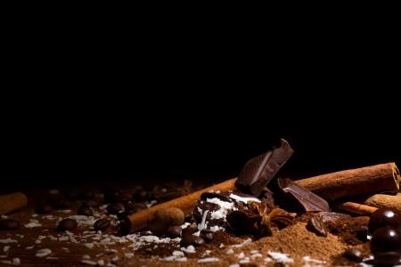 cafe bombon: mezcla de chocolate, granos de caf�, ramas de canela y bomb�n sobre fondo negro oscuro