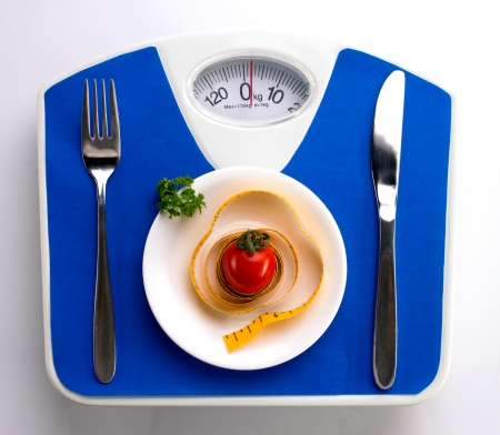 red gram: white plate with tomato and meal, fork and knife on blue scale, on white background