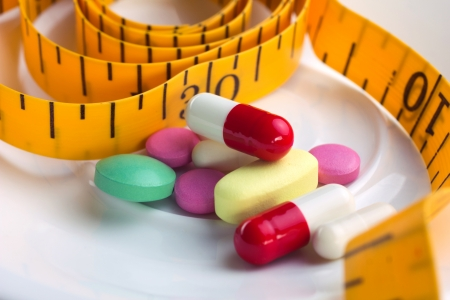 close-up colorful meal and pills on white plate