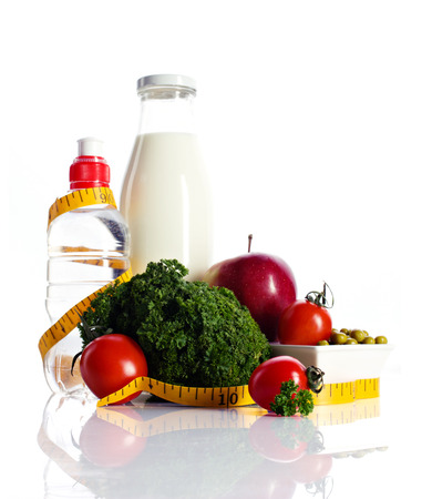 healthy still life- milk and water in bottles, apple, tomato, green peas, curly salad and meal isolated on white photo