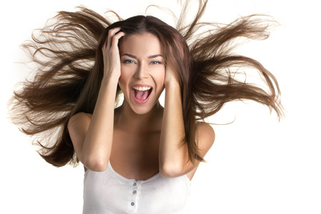 move: young beautiful happy girl with long brown flying hair,  hold on head  and opened mouth on white background