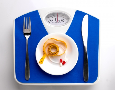 white plate with measuring tape and supplement in capsules, spoon and knife on blue scale, top view photo